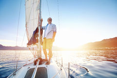 Sunrise sailing boat. Sunrise sailing man on boat in ocean with flare and sunlight on calm morning on the water Stock Images