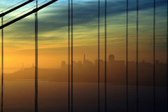 San Francisco sunrise. Yellow to blue skies on the early morning on the San Francisco bay area with the Transamerica building silhouette seen through the cables Royalty Free Stock Photo
