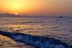 Sunrise, Santorini beach. Sun, waves and sand Royalty Free Stock Photos