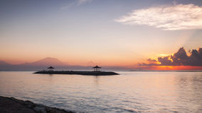 Sunrise at Sanur Beach of bali, Indonesia. Sun rays lite up the thin layers of mist warm up Mount Agung in the background Royalty Free Stock Photo
