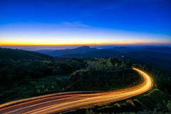 Sunrise scence of car light trail to the top with curve of road. At Doi Inthanon National park in Chiang Mai Province, Thailand stock photos
