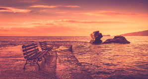 Sunrise scene at the sea. There are two benches and two cliffs into the water Royalty Free Stock Photo