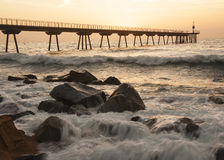 Sunrise at the sea. Orange sunrise behind a Long bridge to the sea where the waves crashes against the rocks Stock Photography