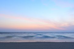 Sunrise at sea. On beach, waves is blurred with long exposure Stock Photo