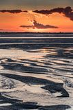 Sunrise on the sea at the Baie de Somme at low tide. Orange sunrise light on the mouth of the Somme River. The sky is reflected in the puddles of the low tide stock image