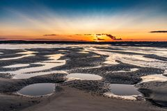 Sunrise on the sea at the Baie de Somme at low tide. Orange sunrise light on the mouth of the Somme River. The sky is reflected in the puddles of the low tide royalty free stock image