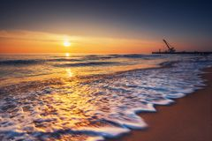 Sunrise on the sea and beach. Waves washing the sand. Industrial crane build new bridge.  royalty free stock image