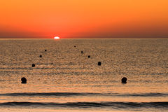 Sunrise at Sea with Buoys Stock Photography