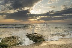 Sunrise from the sea, with great sun colors, rocks with waves and dramatic clouds on the sky on landscape view Stock Photo