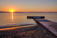 Sunrise on the sea in Moraitika, Greece. View on the sunrise on the sea, the mountains and a wooden pier on the beach Moraitika, island Corfu, Greece Stock Photography
