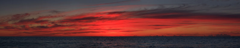 Sunrise sea pan wide. Red saturated wide panoramic sunrise over open ocean horizon dark water and overcast sky Royalty Free Stock Image