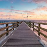 Sunrise at the sea - pier walk during morning hours. Beautiful colors in the sky royalty free stock photography
