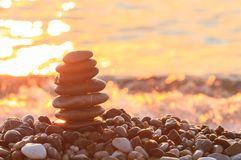 Sunrise on the sea and the pyramid of pebbles royalty free stock photography