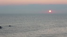 Sunrise Sea Scenery. Sunrise sea scenery with sun in sky and tops of underwater rocks above water. There is zoom out on video stock video footage