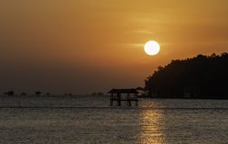 Sunrise from the sea with Silhouette old hut in the sea. In the gulf of Thailand stock images