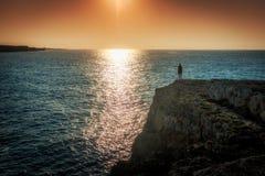 Sunrise at sea of the Spanish island Mallorca. Sunrise at sea of the Spanish island Mallorca, silhouette of man on rocky shore Stock Photo