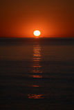 The sunrise from the sea, with the sun centered, red sky and long reflection on the surface of water.  Royalty Free Stock Photos