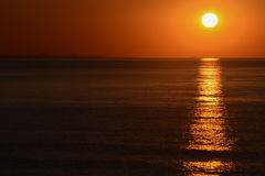 The sunrise from the sea, with the sun on right, orange sky and long reflection on the surface of water Royalty Free Stock Photo