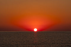 Sunrise at Sea with Sun Touching Water stock images