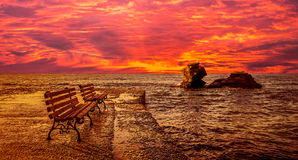 Sunrise at the sea. There are two benches and two cliffs into the water Royalty Free Stock Photos