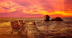 Sunrise at the sea. There are two benches and two cliffs into the water Stock Photography