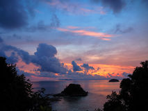 Sunrise sea view with small island and colorful sky through gree Stock Photos