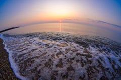 Sunrise by the sea with wave splashing on the sand beach, Vama V Royalty Free Stock Images