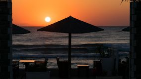 Sunrise on the seafront with reed sun silhouette umbrellas, the sea with waves and dinner table. This photo was taken at the shore of the Mediterranean Sea in stock image