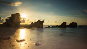 Sunrise seascape with natural stone arch. Seascape with natural stone arch at sunrise with light flare in Rayong beach, Thailand. Big stopper filter for Long royalty free stock photo