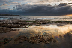 Sunrise seascape with rocks and reflection of clouds Stock Photos