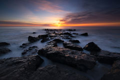 Sunrise seascape from a rocky Jetty Stock Photo