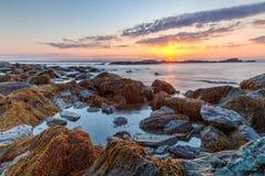 Rocky Sunrise Seascape. Colorful orange, pink and blue HDR sunrise seascape of rocky coastline at Sachuest Point Wildlife Refuge in Middletown Rhode Island, USA stock image