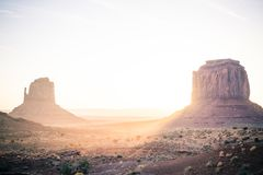 Sunrise in The Sedona Monument Valley. The sun rises in the distance over the rock formations in Sedona Monument Valley. Two large rocks draw the eye towards the royalty free stock image
