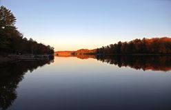 Sunrise on a calm lake in the Fall. Sunrise shines on distant hills and calm lake casting shadows and reflections Royalty Free Stock Photos