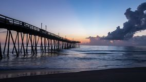 Beautiful ocean sunrise and gentle waves beside an old wooden fishing pier extending far out into the sea. Sunrise shines on the tall white clouds and the calm stock image