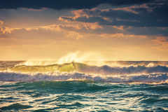 Sunrise and shining waves in ocean. Dramatic sunrise over the shining waves in the ocean Royalty Free Stock Images