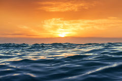 Sunrise and shining waves in ocean Royalty Free Stock Image