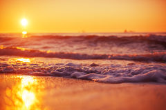 Sunrise and shining waves in ocean. Sunrise light shining on ocean wave with orange tones Stock Photography