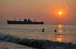 Sunrise with a ship and swimmers Royalty Free Stock Photography