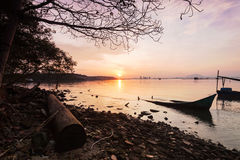 Sunrise by the shore. With silhouette of broken boat royalty free stock photos
