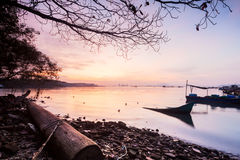 Sunrise by the shore. With silhouette of broken boat royalty free stock image