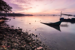 Sunrise by the shore. With silhouette of broken boat stock photo