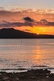 Sunrise shows half sun over Rangitoto Volcano near Auckland. Auckland, New Zealand - March 2, 2017: Sunrise over Rangitoto Volcano, shot from Tapapuna Beach in Stock Image