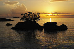 Sunrise with sihouetted rocks, Malawi. Royalty Free Stock Images