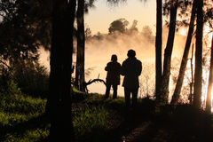 Sunrise silhouette of 2 people on riverbank. 2 photographers are silhouetted as they stand on river bank as mist rises above the water at sunrise Royalty Free Stock Photos