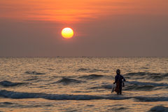 The sunrise and silhouette image of fisherman in sea Royalty Free Stock Photo
