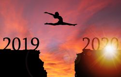 Free Sunrise Silhouette Of Girl Leaping Over Cliff Toward New Year 2020 Stock Photos - 143395943