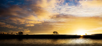 Sunrise silhouette over water Stock Images