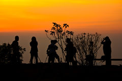 Sunrise with silhouette of people Stock Photos