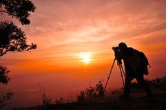 Sunrise silhouette of traveler man. On orange sky Stock Image